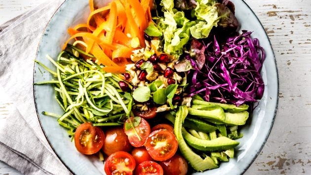 Vegan buddha bowl. Bowl with fresh raw vegetables - cabbage, carrot, zucchini, lettuce, watercress salad, tomatoes cherry and avocado, nuts and pomegranate